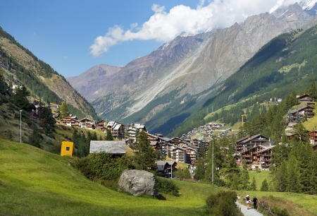 typical little resort town in the Swiss Alps with views of the mountain peaks photo