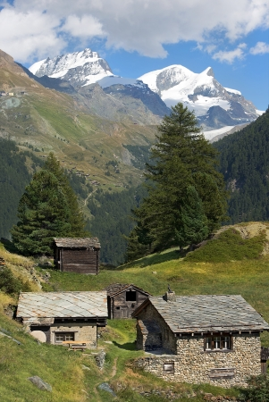 beautiful alpine landscape, stone houses in the Swiss Alps with views of the snowy peaks photo