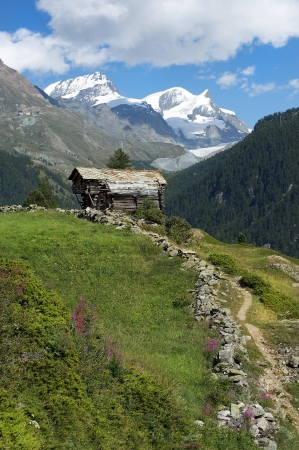 beautiful alpine landscape, wooden chalet in the Swiss Alps with views of snowy peaks photo