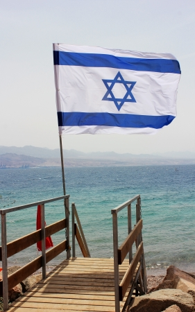 Israeli flag against the backdrop of the Red Sea, an invitation to to rest at the resort of Eilat, Israel photo