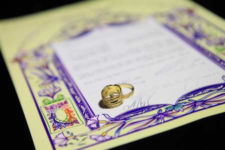 hebrew script: wedding rings and Ketubah - a prenuptial agreement in jewish religious tradition Stock Photo