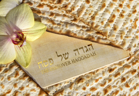 spring holiday of Passover and its attributes, with matzo and Haggadah in hebrew and english - Happy Passover Stock Photo