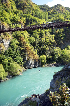ropejumping from the bridge across the turbulent river in the mountains of New Zealand