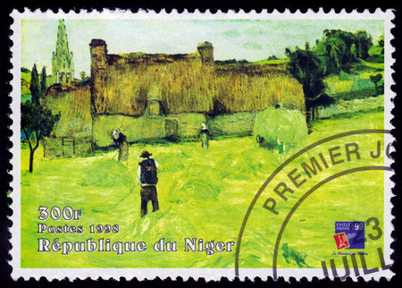 REPUBLIC NIGER - CIRCA 1998  A stamp printed in Niger shows painting by Paul Gauguin, Haymaking in Brittany, Musee d Orsay, circa 1998 Stock Photo