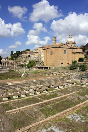 antique ruins of famous ancient Roman Forum on the background of bright blue sky with unusual clouds, Rome, Italy