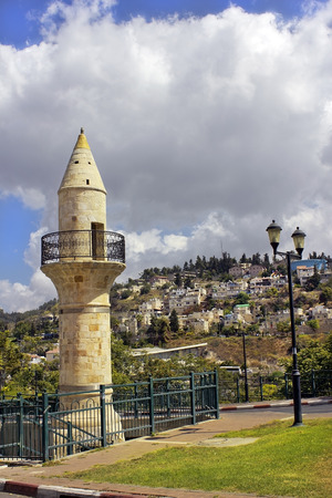 old minaret in Safed on the background of a residential area on Mount Canaan, Israel