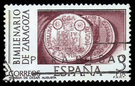 reign: Spain - CIRCA 1976: stamp printed in Spain shows roman coins from the reign of Cesar Augusta, Bimilenary of Zaragoza, circa 1976 Stock Photo