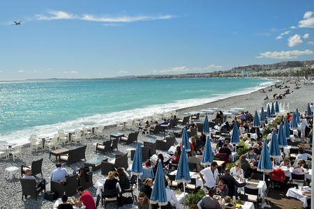 NICE, FRANCE, French Riviera - March 23: tourists and vacationers sitting in the cafe on the beach on March 23, 2014, Nice, France
