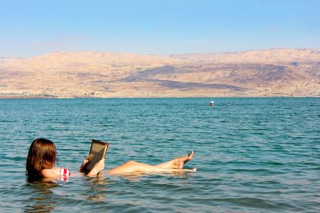 젊은 여자가 이스라엘에서 죽은 바다의 물에 떠있는 책을 읽습니다