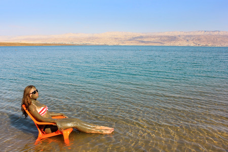 young girl smeared with therapeutic mud sunbathes sitting on a chair in the Dead Sea, Israel