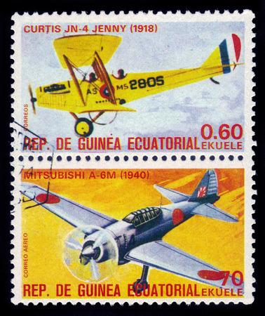 curtis: Equatorial Guinea, Republic - CIRCA 1979: A stamp printed in Equatorial Guinean shows aircrafts Curtis JN 4 Jenny and Mitsubishi A-6M, circa 1979