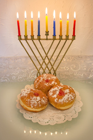 hanukah: Hanukkah menorah with burning candles and traditional doughnuts