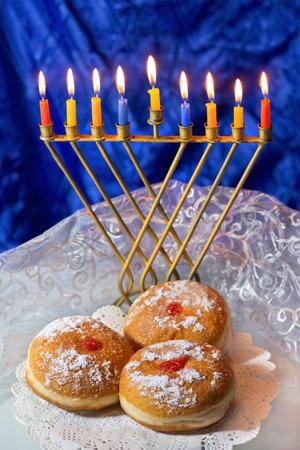 hanukka: Hanukkah menorah with burning candles and traditional doughnuts