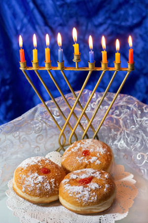 hanukka: Hanukkah menorah with burning candles and traditional doughnuts