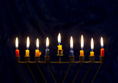 Hanukkah menorah (nine-branched candelabrum) with burning colored candles on a dark blue background photo