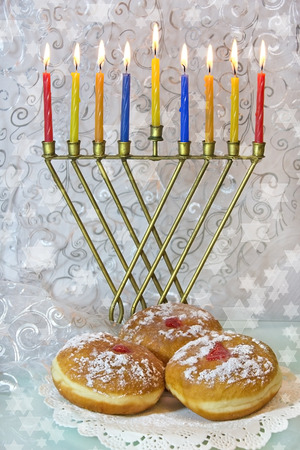 hanukka: Hanukkah menorah with burning colored candles and traditional doughnuts