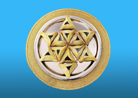 Star of David made from Hamantaschen cookies for Jewish festival of Purim on a blue background