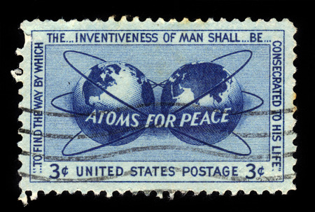 encircling: UNITED STATES OF AMERICA - CIRCA 1955: a stamp printed in USA, shows atomic energy encircling the hemispheres, atoms for peace Issue, circa 1955
