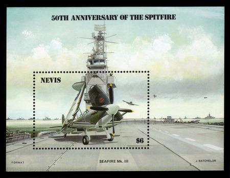 avion de chasse: Nevis - CIRCA 1986: Un bloc-feuillet imprim� par NEVIS montre Spitfire avion de chasse sur le pont d'un porte-avions, 50e anniversaire, circa 1986 �ditoriale