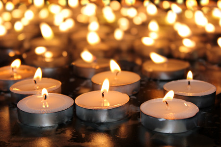 burning memorial candles on dark background