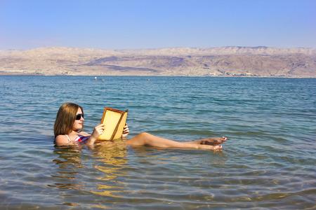 아름 다운 젊은 여자는 이스라엘 사해의 물에 떠있는 책을 읽습니다