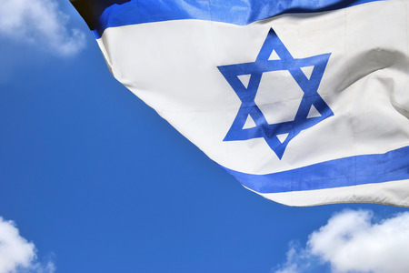 Star of David on a blue and white Israeli flag on background the bright sky