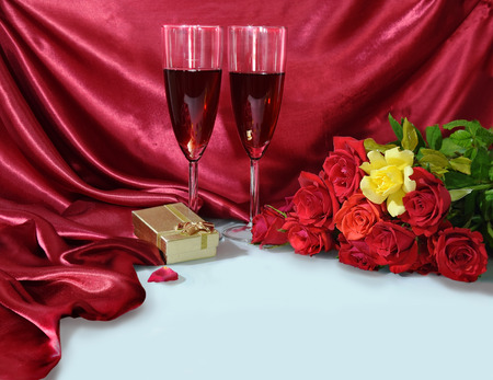 red gift box: two glasses of red wine, a bouquet of red roses and one yellow, gift box on the background of purple silk fabric - romantic greeting card for Valentines Day