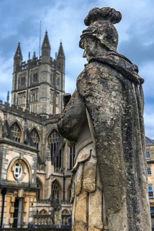 somerset: old stone statue of a roman soldier in the background of Bath Abbey, Somerset, England.