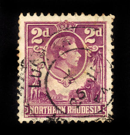 vi: NORTHERN RHODESIA - CIRCA 1940: A stamp printed in United Kingdom shows portrait King George VI on the background of african animals, circa 1940