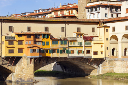 historical reflections: medieval stone bridge Ponte Vecchio over the Arno River in Florence, Tuscany, Italy