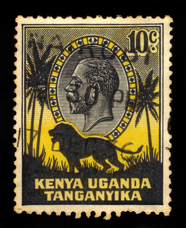 tanganyika: KENYA, UGANDA AND TANGANYIKA - CIRCA 1935: a stamp printed in East Africa showing image of a lion and palm trees against the portrait of King George V, circa 1935.