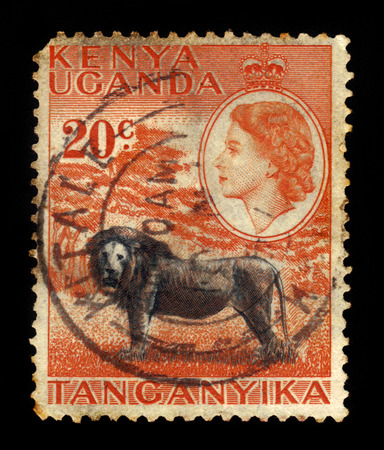KENYA, UGANDA AND TANGANYIKA - CIRCA 1954: a stamp printed in East Africa showing image of a lion against the portrait of Queen Elizabeth II, circa 1954