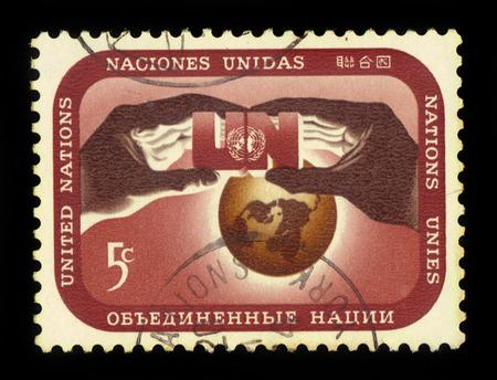 united nations: Naciones Unidas, Nueva York - alrededor de 1967: un sello impreso en Nueva York muestra las manos que sostienen un símbolo de las Naciones Unidas contra el fondo del mundo, alrededor de 1967
