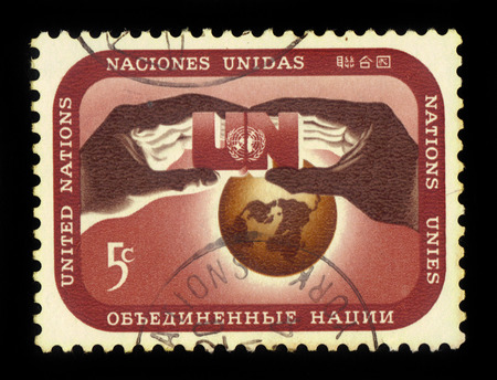un used: United Nations, New York - CIRCA 1967: a stamp printed in New York shows hands holding a symbol of United Nations against the background of the globe, circa 1967 Editorial