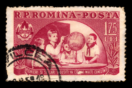 pioneers: ROMANIA - CIRCA 1954: A stamp printed in Romania shows young pioneers looking at a globe, circa 1954
