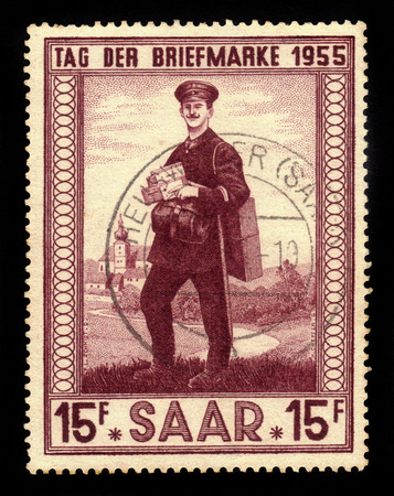 saar: Germany, Saarland - CIRCA 1955: a stamp printed in the Saar, Germany shows postman and church of Illingen, circa 1955