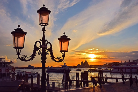 water bus: romantic views of the Grand Canal in Venice at sunset, with vintage street lamp in the foreground