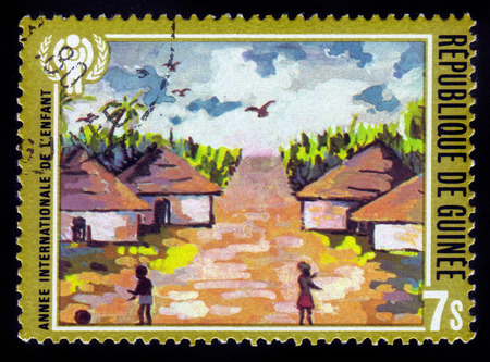 Guinea - CIRCA 1980: stamp printed in Guinea shows children in african village, series year of the child, circa 1980