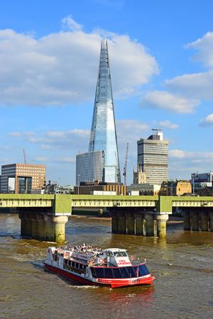 shard: LONDON, ENGLAND - May 24,2017: pleasure boat on the River Thames against the backdrop of Cannon Street Railway Bridge and the skyscraper Shard, London, UK