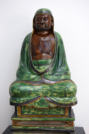 LONDON, ENGLAND - May 24,2017: sculpture (stoneware with green and brown glazes) seated Bodhidharma, ming dynasty, was buddhist monk, first chinese patriarch, Victoria and Albert Museum, London, UK Editorial