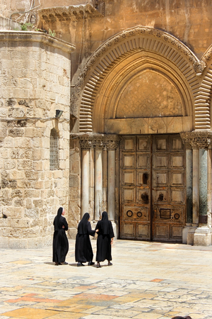 catholic nuns: catholic nuns at the closed gates of the temple of the Holy Sepulcher, old city of Jerusalem, Israel Editorial