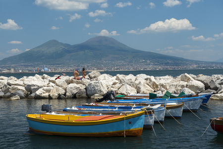 Naples, Italy - may 18, 2017: fishing boats in the port of Naples and view of Mount Vesuvius and Gulf of Naples in good weather, Naples, Italy Editorial