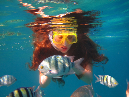 young girl swimming under water among tropical fish, Red Sea, Eilat, Israel