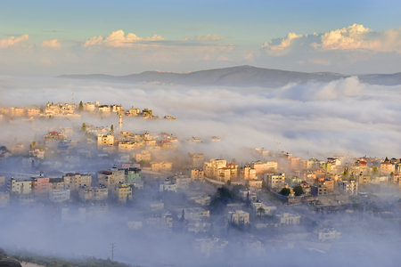 view of the shrouded in the morning fog biblical village Cana of Galilee ( Kafr Kanna ), neighborhood Nazareth in Israel, place where Jesus Christ showed first miracle