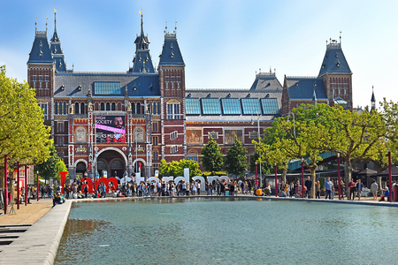 Amsterdam, the Netherlands - May 20, 2018: main facade of the Rijksmuseum (State museum), letters I AMsterdam - one of known sights of the city and pond