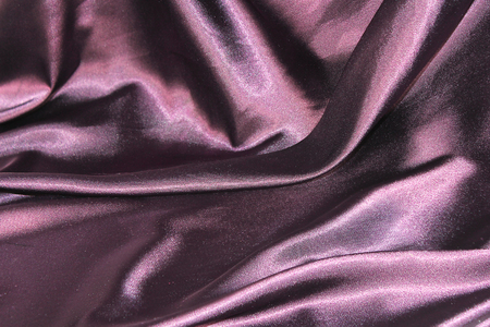 undulating folds of the fabric of purple silk as festive background