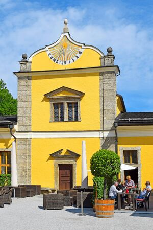Salzburg, Austria - May 25, 2019 : Hellbrunn Palace (Schloss Hellbrunn), summer residence of the Archbishop of Salzburg, outbuilding with a sundial on the facade 에디토리얼