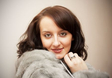 Beauty Girl with brown hair in a fur coat photo