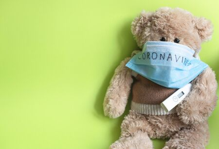 """A soft toy bear in a protective medical mask with the inscription """"coronavirus"""" and a thermometer, sits on a green background. Concept of quarantine of schools and kindergartens, home education."""