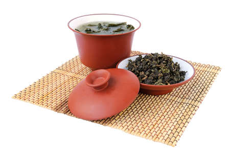 tea break: Chinese green tea in the ceramic bowl with cover and tea leaves